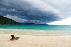Сиротливый шезлонг на дезертированном пляже, против предпосылки o Стоковая Фотография