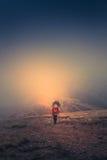 Сиротливый hiker с рюкзаком идя вдоль следа на верхней части горы на туманном времени дня Стоковые Изображения RF