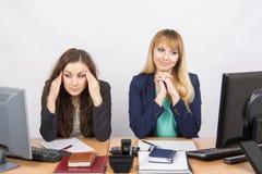 Ситуация в офисе - девушке счастливо смотря экран компьютера, другое девушка при головная боль смотря экран Стоковые Фото