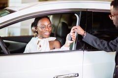 Ситуация продаж в автосалоне, молодые африканские пары получает ключ для нового автомобиля стоковое изображение rf