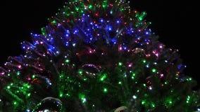 Сияющая высокая ель рождества украшенная с гирляндами и пестроткаными шариками против ночного неба меньшие падения снега сток-видео