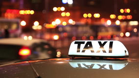 Сияющая надпись такси против проходить автомобили на улице ночи города акции видеоматериалы