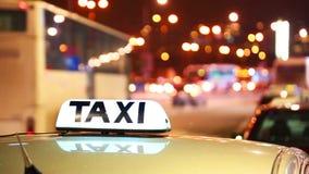 Сияющая надпись такси против проходить автомобили на улице ночи города видеоматериал