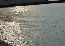 Сияющая серебряная вода на море Pebble Beach, рано утром восходе солнца Стоковые Фото