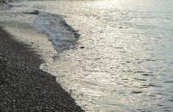 Сияющая серебряная вода на море Pebble Beach, рано утром восходе солнца Стоковые Изображения