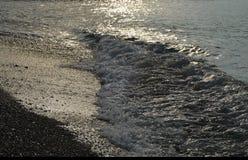 Сияющая серебряная вода на море Pebble Beach, рано утром восходе солнца Стоковая Фотография RF