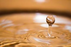 Сияющее падение воды покрашенное апельсина изолированный Стоковые Фото