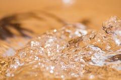 Сияющее падение воды покрашенное апельсина изолированный Стоковая Фотография
