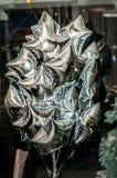 Сияющие серебряные воздушные шары в форме звезд Стоковые Изображения