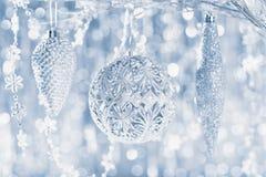 Сияющие серебряные орнаменты рождества вися на дереве, с defocused светами рождества на заднем плане звезды абстрактной картины к стоковое изображение rf