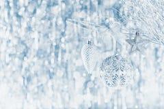 Сияющие серебряные орнаменты рождества вися на дереве, с defocused светами рождества стоковое фото