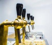 сияющие faucets пива в кранах бара металлических выстукивают на ресторане, Стоковое Изображение