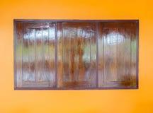 Сияющий ретро стиль деревянное Windows на оранжевой стене используемой как шаблон Стоковое Изображение