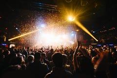 Сияющий confetti радуги во время концерта и силуэты толпы с их руками вверх Стоковая Фотография RF