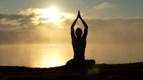 Сияющий yogi сидит в лотосе на банке озера и молит на заходе солнца в замедленном движении сток-видео