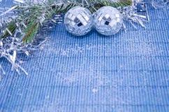 2 сияющих шарика диско на ветви ели покрытой с снегом Стоковые Фото
