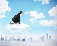 Сидение на корточках женщины на верхней части облака Стоковые Фотографии RF