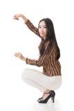 Сидение на корточках и владение женщины что-то Стоковое Изображение