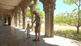 Сидение на корточках маленькой девочки отца в тени галереи готического здания сток-видео