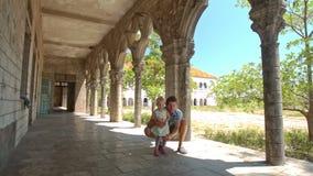 Сидение на корточках маленькой девочки отца в тени галереи готического здания акции видеоматериалы
