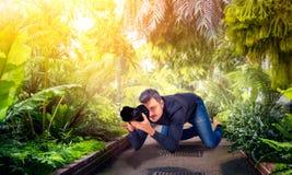 Сидение на корточках мужчины, фотографируя зеленую природу на камере Стоковые Фотографии RF