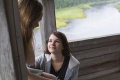 Сидеть девушки 2 подростков говоря в газебо около реки Лето Стоковая Фотография