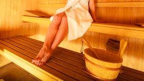 Сидеть женщины ослабленный в деревянной сауне Стоковая Фотография