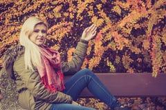 Сидеть женщины ослабляя на стенде в осеннем парке Стоковое Изображение RF