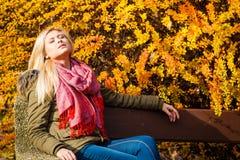 Сидеть женщины ослабляя на стенде в осеннем парке Стоковая Фотография
