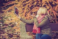 Сидеть женщины ослабляя на стенде в парке используя таблетку Стоковая Фотография