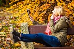 Сидеть женщины ослабляя на стенде в парке используя таблетку Стоковое Изображение