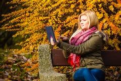 Сидеть женщины ослабляя на стенде в парке используя таблетку Стоковая Фотография RF