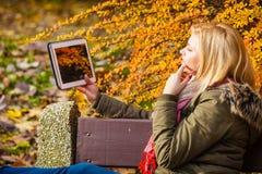 Сидеть женщины ослабляя на стенде в парке используя таблетку Стоковое Изображение RF