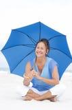 Пляж зонтика привлекательной возмужалой женщины голубой Стоковое фото RF