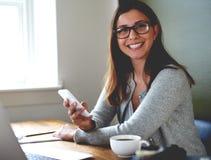 Сидеть женщины усмехаясь на столе в домашнем офисе Стоковые Изображения