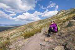 Сидеть женщины Hiker отдыхая в тропе Guadarrama Стоковые Изображения RF