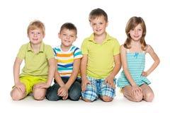 Сидеть 4 жизнерадостных дет Стоковая Фотография RF
