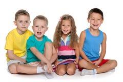 Сидеть 4 жизнерадостных дет Стоковое Фото