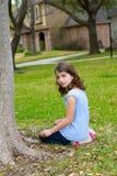 Сидеть красивой девушки ребенк усмехаясь на лужайке парка ослабил Стоковое Изображение