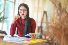 Сидеть молодого женского предпринимателя работая на столе печатая дальше его Стоковое Изображение RF