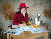 Сидеть молодого женского предпринимателя работая на столе печатая дальше его Стоковая Фотография