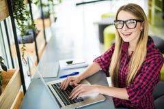 Сидеть молодого женского предпринимателя работая на столе печатая на ее портативном компьютере в офисе, осматривает сверху Стоковое Изображение RF