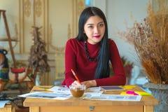 Сидеть молодого женского предпринимателя работая на столе печатая o Стоковое фото RF