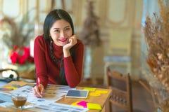 Сидеть молодого женского предпринимателя работая на столе печатая o Стоковые Изображения