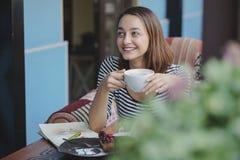 Сидеть молодой женщины крытый в городском кафе Стоковое Изображение