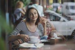 Сидеть молодой женщины крытый в городском кафе Стоковые Изображения