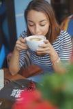 Сидеть молодой женщины крытый в городском кафе Стоковые Фотографии RF
