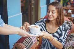 Сидеть молодой женщины крытый в городском кафе Стоковая Фотография RF