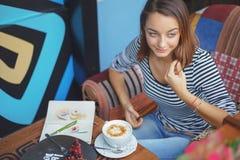 Сидеть молодой женщины крытый в городском кафе Стоковые Изображения RF