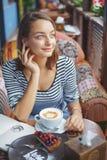 Сидеть молодой женщины крытый в городском кафе Стоковое Фото
